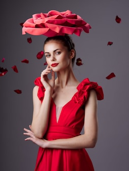 Woman in a beautiful red dress with a rose and rose petals on a red surface