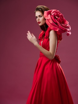 Woman in a beautiful red dress with a rose and rose petals