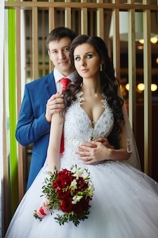 Woman in a beautiful white dress and a man in a blue suit hugging near the window