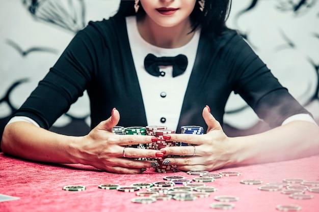 카드, 칩, 알코올 근접 촬영이 있는 테이블에 있는 카지노에서 아름다운 젊은 성공적인 도박