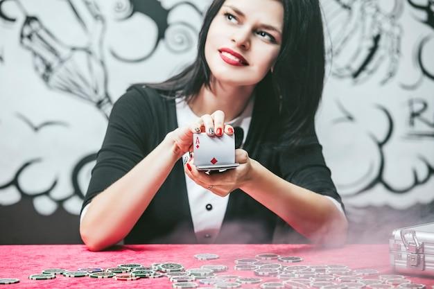 카드, 칩, 알코올이 있는 테이블에서 카지노에서 아름다운 젊은 성공적인 도박