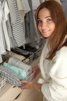 Woman beautifully put things into containers. clothes storage.