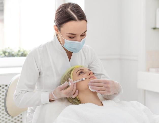 Donna alla clinica di bellezza per il trattamento di riempimento