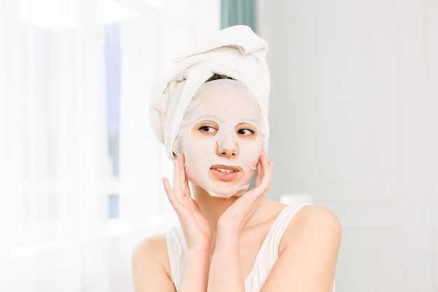 女性の美しさの顔。テキスタイルシートの顔のマスクを適用する新鮮なナチュラルメイクで笑顔の若い女性のクローズアップ。白い化粧品のマスクを持つ魅力的な幸せな少女の肖像画。