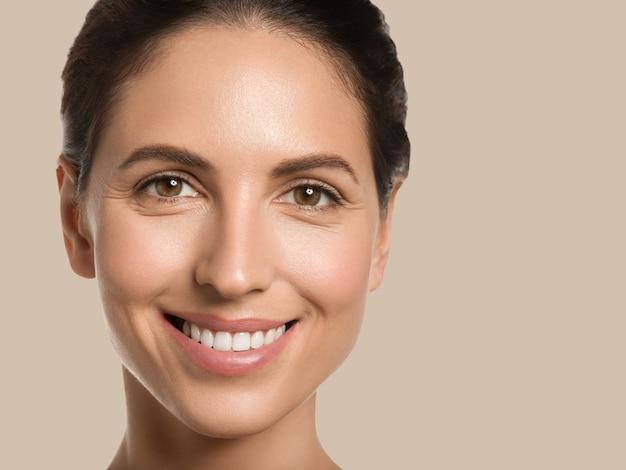 여자 아름다움 얼굴 건강 한 피부 자연 깨끗 한 신선한 얼굴. 보기를 닫습니다. 색상 배경입니다. 갈색