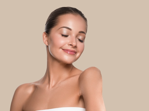 Woman beauty face healthy skin natural makeup beautiful young model. color background. brown