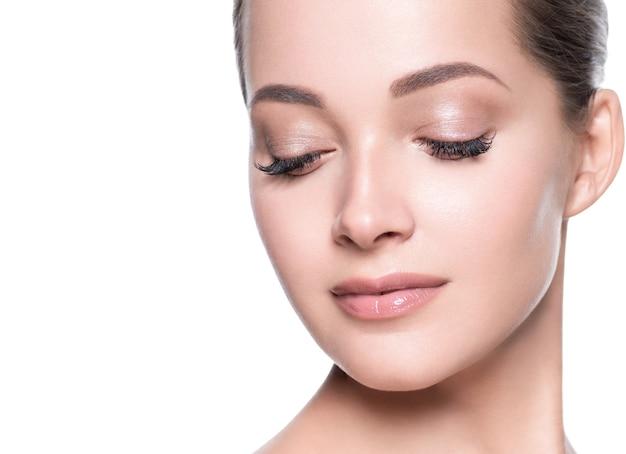 女性美顔健康肌ナチュラルメイク美しい若いモデル。スタジオショット。