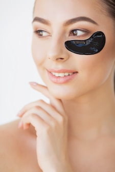 Woman beauty face with mask under eyes. beautiful female with natural makeup and black collagen patches on fresh facial skin