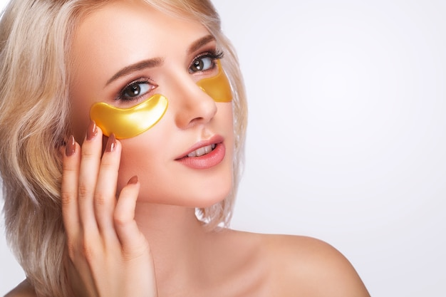 Woman beauty face with mask under eyes. beautiful female with natural makeup and gold collagen patches on fresh facial skin.