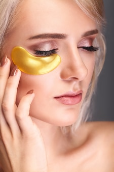 Woman beauty face with mask under eyes. beautiful female with natural makeup and gold collagen patches.