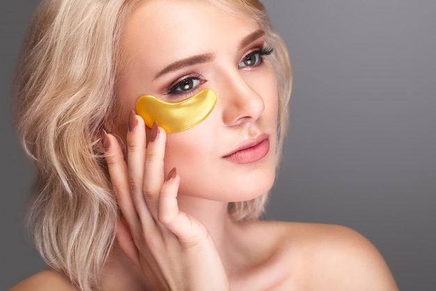 Woman beauty face with patch under eyes