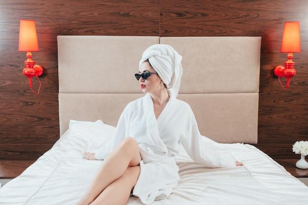 女性の美しさ。ベッドでポーズをとるバスローブの女性。素足。サングラスとタオルターバン。高級ホテルの部屋のインテリア。