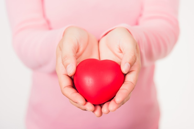 Женщина красоты руки держит красное сердце для оказания помощи пожертвования медицинского здравоохранения