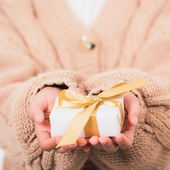Женщина красоты руки держа небольшую подарочную коробку подарка обернутой бумагой с лентой