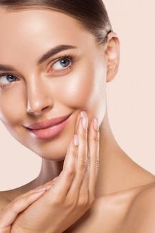 Женщина красоты здоровая чистая кожа макияж молодая модель рука касаясь лица. бежевый фон.