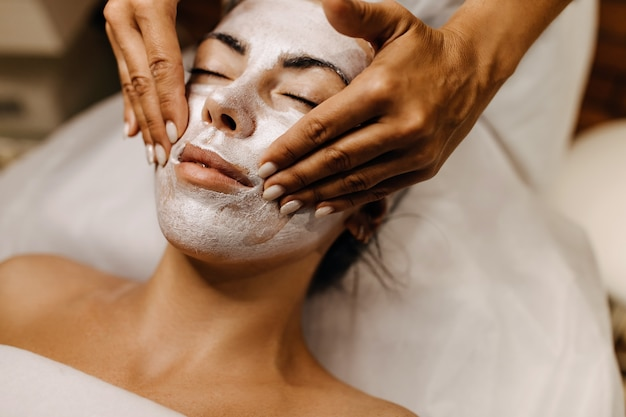 Woman at a beauty salon having a face massage with a shimmery cream mask