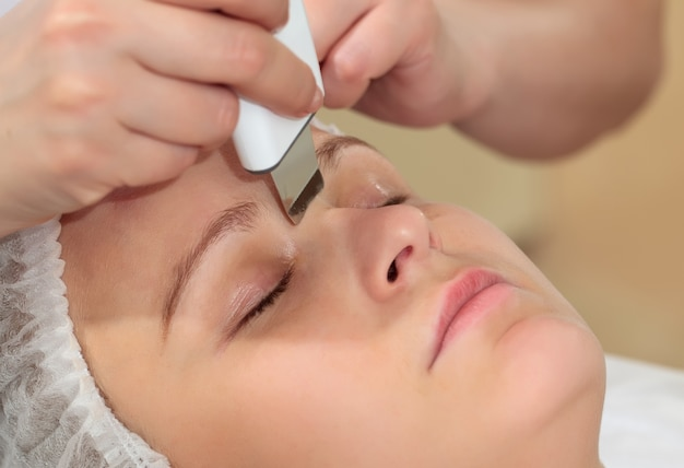 A woman at beauty spa getting facial treatment with ultrasonic facial cleaning