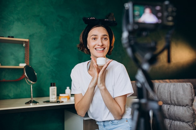 Woman beauty vlogger filming vlog about creams