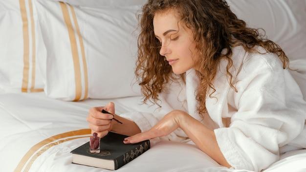 Woman in bed applying nail polish