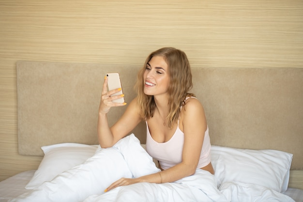 Woman in bed checking social apps with smartphone.