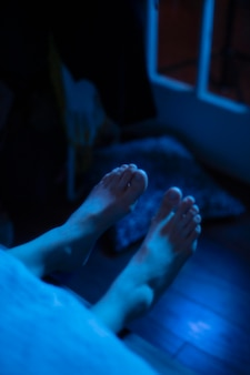 Woman in bed at home with mysterious lights around her