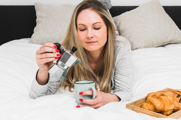 Woman on bed pouring coffee