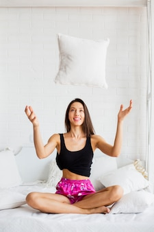 Woman in bed throwing pillow up