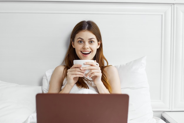 Woman in bed with a coffee mug and laptop