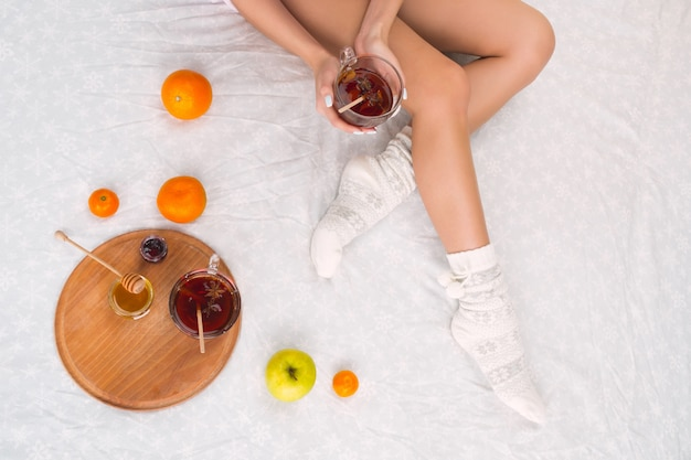 Woman on bed with cup of tea and fruits, top view. female legs in warm woolen socks.