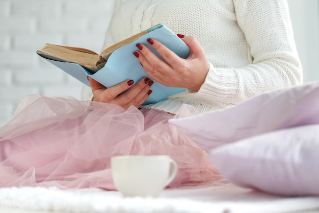 Woman on the bed with old book and cup of tea