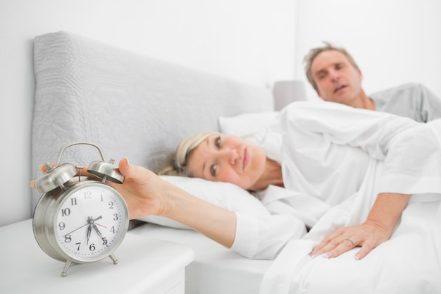 Woman in bed with partner turning off alarm clock