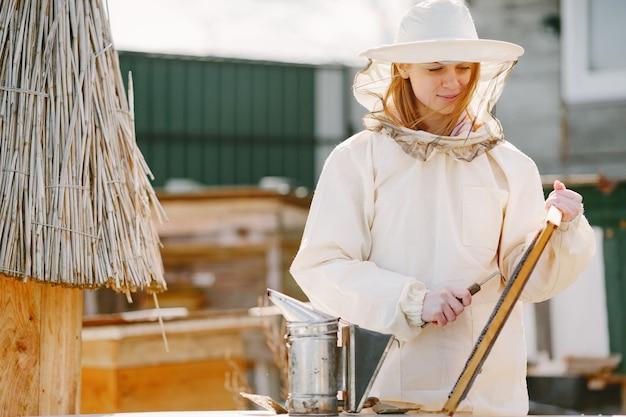 Пчеловод женщина ухаживает за пчелами. женщина работает в комбинезоне на пасеке.