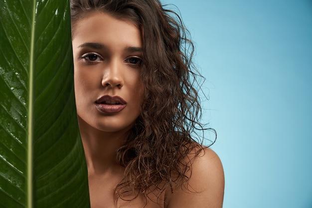 블루에 고립 된 큰 녹색 잎 뒤에 여자