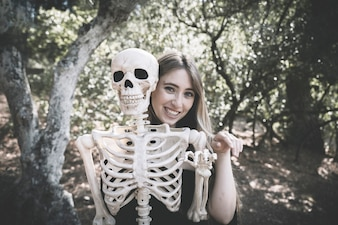 Woman behind skeleton with raising hand