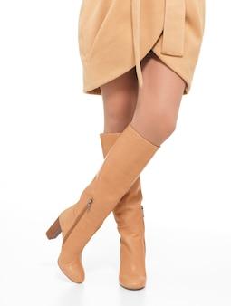 Donna in stivali autunnali beige in piedi isolato su bianco