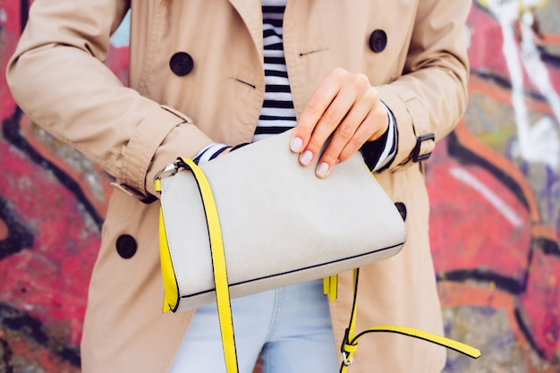 Woman in beige coat and jeans holding a lady's handbag on a background of graffiti outdoors