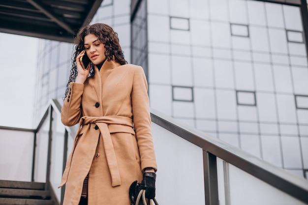 Woman in beige coat walking in the city