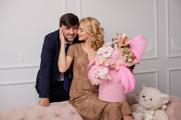 Woman in the beige dress sitting on the couch with the box of flowers hugging her man