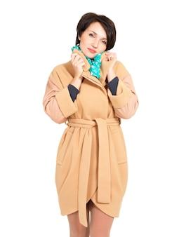 Donna in cappotto beige caduta con sciarpa verde in piedi isolato su bianco