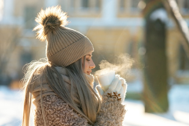 Woman in beige fur coat, hat with pompon, mittens holding steaming white cup of hot tea/coffee, sunny winter day