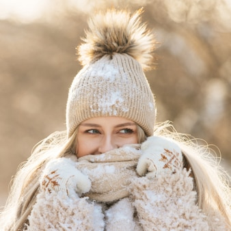 Woman in beige hat with fur pompon, warm scarf, white gloves covered with snow at sunny winter day