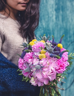 Woman in beige sweater with a mixed flower bouquet.