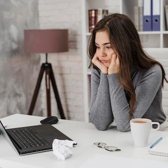 Женщина скучает во время работы из дома