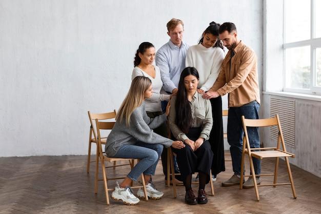 集団療法セッションで人々に慰められている女性