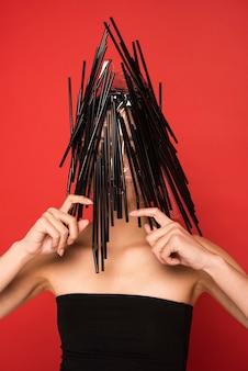 プラスチック製の黒いストローで覆われている女性