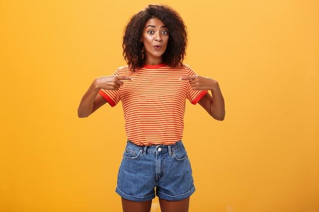 친구에게 새로운 직업을 얻었다고 기뻐하는 여성은 세련된 데님 반바지와 줄무늬 티셔츠를 입고 주황색 배경 위에 서서 기뻐하며 만족스러운 표정으로 자신을 가리키고 있습니다.