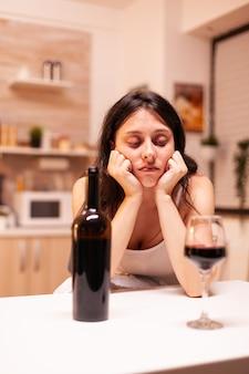 うつ病とストレスのために二日酔いしている女性。アルコール依存症の問題で疲れ果てた不幸な人の病気と不安感。