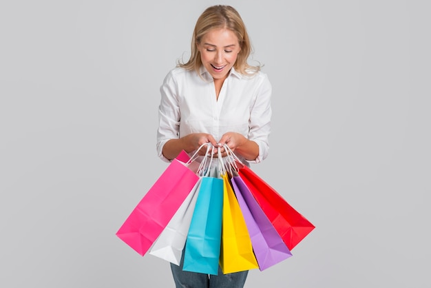 Woman being happy about many shopping bags that she's hoding