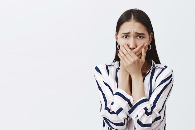 嫌がらせを受けている女性は、誰かに話すことを恐れています。縞模様のブラウスと流行のイヤリングで怖い気になる女性、悲鳴を上げないように手のひらで口を覆い、眉をひそめ、灰色の壁を恐れている