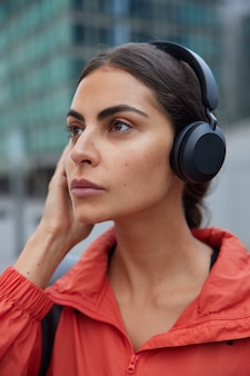 Woman being music lover enjoys favorite composition from playlist popular song listens to radio broadcasting wears red jacket poes against blurred